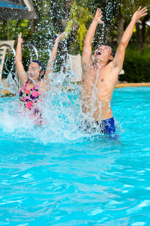 Father and daughter are having fun splashing in the pool photo