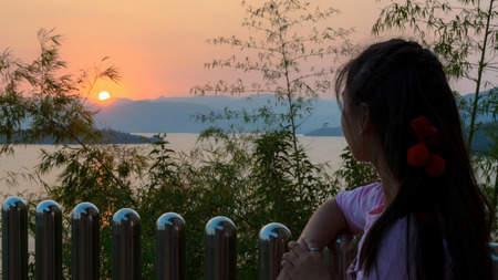 Happy young woman standing on the hill watching the sunset over the lake in Kaeng Kra Chan National Park, Phetchaburi Province, Thailand, 16 9 widescreen photo