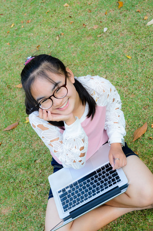 Lovely girl is happy with a laptop on lawn in park photo
