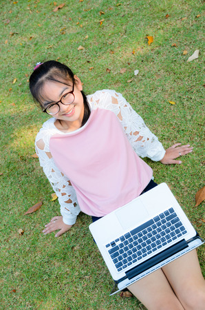 Cute girl is happy with notebook on grass in park photo