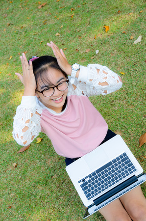 Cute girl is happy with notebook on grass in park