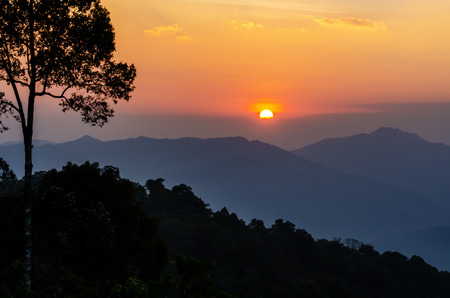 High angle view beautiful sunset over mountain range from Panoen Thung scenic point at Kaeng Krachan National Park Phetchaburi province in Thailand photo