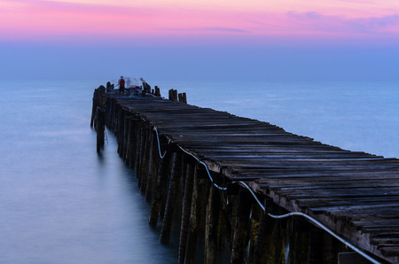 Silhouette fisherman on the old wooden bridge and sea at sunrise in rural Thailand. photo