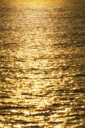 Background of water with golden sunrise reflections photo