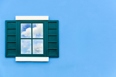 Sky and cloud reflection in green window glass on blue wall of house, Italy retro style photo