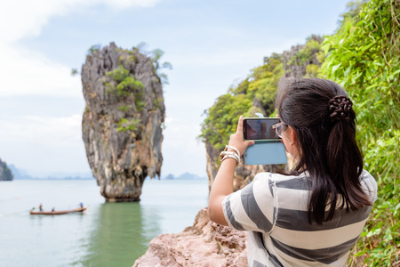phang nga: Women tourist he is shooting a beautiful scenic view by mobile phone at Khao Tapu or James Bond Island in Ao Phang Nga Bay National Park Thailand