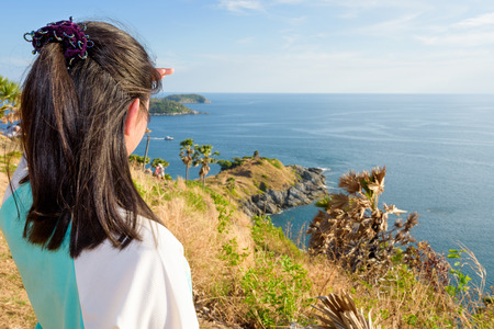 famous women: Back of the women tourist looking at beautiful nature sea and island with a happy on the mountain viewpoint at Laem Phromthep Cape a famous attractions of Phuket Province in Thailand