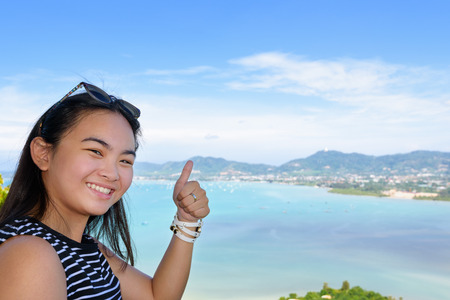 raised viewpoint: Women tourist smiling happy along with thumb raised expresses admiration for beautiful landscape of the sea and island on Khao-Khad mountain high viewpoint in Phuket Province, Thailand Stock Photo