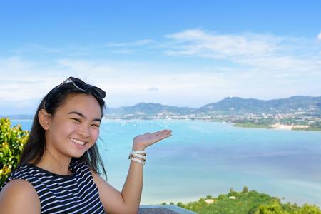 invitando: Mujeres tur�stica sonriendo felices de mostrar su mano invit�ndolos a ver el hermoso paisaje de mar en Khao-Khad punto de vista de la monta�a atracciones famosas en la provincia de Phuket, Tailandia