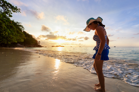 water play: Girl in a swimsuit standing sand and water play with happiness during sunrise on the beach of Honeymoon Bay at Koh Miang, Similan Islands National Park, Phang Nga, Thailand Stock Photo