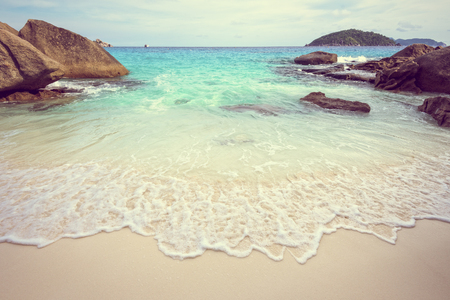 playas tropicales: Vintage style beautiful nature of blue sea sand and white waves on small beach near the rocks during summer at Koh Miang island in Mu Ko Similan National Park, Phang Nga province, Thailand