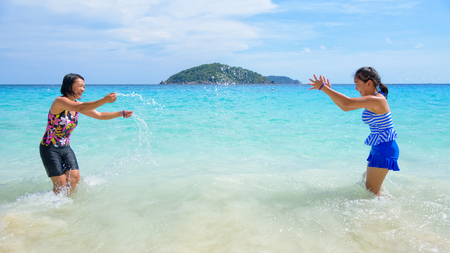 blue widescreen widescreen: Mother and daughter in a swimsuit playing on the blue sea near the beach with happiness during summer at Koh Miang Island, Mu Ko Similan National Park, Phang Nga, Thailand, 16:9 widescreen Stock Photo