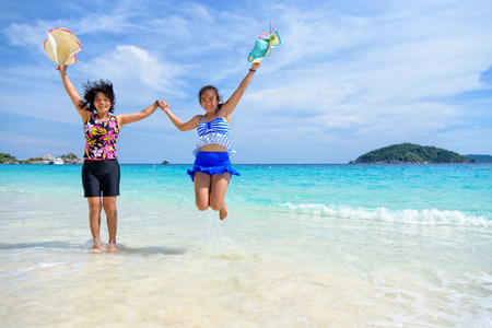 Mother and daughter wear a swimsuit playing in the blue sea near the beach with happiness during summer at Koh Miang Island, Mu Ko Similan National Park, Phang Nga province, Thailand Stock Photo