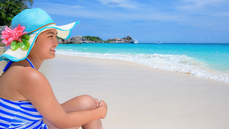 blue widescreen widescreen: Girl in a blue swimwear sitting a happy on the beach with the sea as background during summer at Koh Miang Island, Mu Ko Similan National Park, Phang Nga, Thailand, 16:9 widescreen