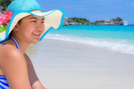 girl on a beautiful background: Girl in a blue swimwear sitting a happy on the beach with the sea as background during summer at Koh Miang Island, Mu Ko Similan National Park, Phang Nga province, Thailand