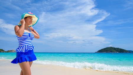 widescreen: Beautiful woman in a blue striped swimsuit wear a hat standing and look at the sea and sky in summer on the beach of Koh Miang Island, Mu Ko Similan National Park, Phang Nga, Thailand, 16:9 widescreen