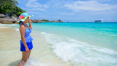 blue widescreen widescreen: Beautiful woman in a blue striped swimsuit and hat standing poses on beach of sea under a summer sky at Koh Miang Island in Mu Ko Similan National Park, Phang Nga Province, Thailand, 16:9 widescreen