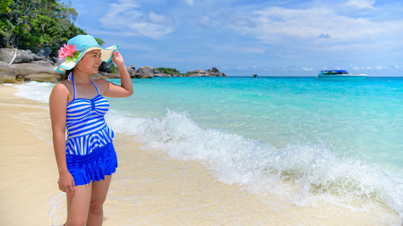 widescreen: Beautiful woman in a blue striped swimsuit and hat standing poses on beach of sea under a summer sky at Koh Miang Island in Mu Ko Similan National Park, Phang Nga, Thailand, 16:9 widescreen Stock Photo