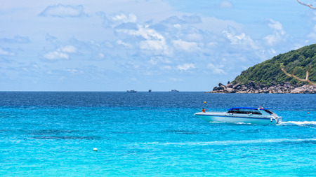 wide screen: White speed boat was running slowly on the blue sea surface in front of Koh Miang Island under the summer sky and beautiful nature in Mu Ko Similan National Park, Phang Nga, Thailand, 16:9 wide screen Stock Photo
