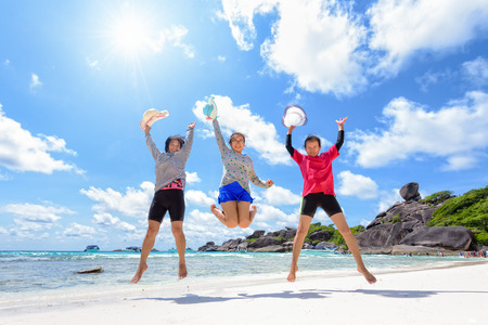 three persons: family jumping on beach near the sea under the sky clouds and sun of summer at Similan Island in Mu Ko Similan National Park, Phang Nga province, Thailand