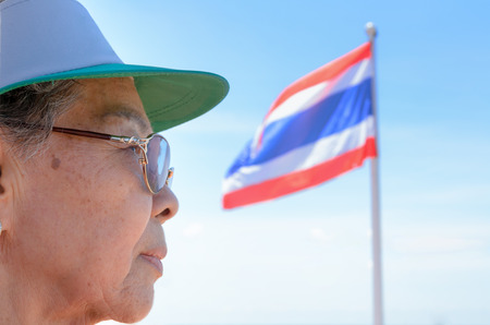 face side: Face side old women Thai people and Thailand flag on a blue sky background Stock Photo