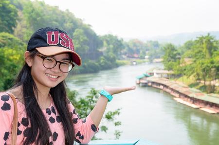 show hands: Muchacha turística que muestran las manos invita a visitar el hermoso paisaje de puente de ferrocarril de la muerte sobre el río Kwai Noi en Krasae punto de vista de la cueva en la provincia de Kanchanaburi, Tailandia Foto de archivo
