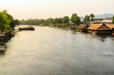 High angle view from bridge, beautiful landscape of Kwai Yai River at sunset and lifestyle of people on the waterfront in Kanchanaburi Province, Thailand