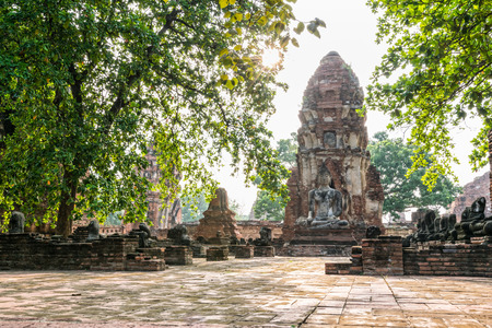 Buddha statue sitting position at front of pagoda under sun light surround by trees and ancient ruins of Wat Phra Mahathat temple in Phra Nakhon Si Ayutthaya Historical Park, Thailand Stock Photo