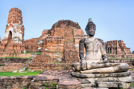 Ancient ruins of pagoda and old buddha statue at Wat Phra Mahathat temple is a famous attractions in Phra Nakhon Si Ayutthaya Historical Park, Thailand