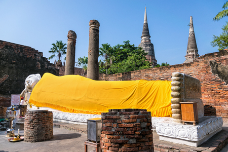 phra nakhon si ayutthaya: Buddha statues are white covered with yellow robe poses sleep amidst ancient ruins at Wat Yai Chai Mongkon temple in Phra Nakhon Si Ayutthaya Historical Park, Ayutthaya Province, Thailand