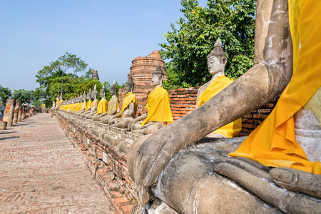 Row of Buddha statue sitting at Wat Yai Chaimongkol temple in Phra Nakhon Si Ayutthaya Historical Park, Ayutthaya Province, Thailand Stock Photo