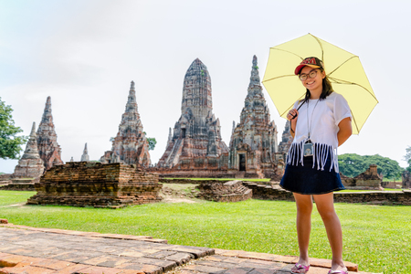 Tourist cute teenage girl wearing glasses with a camera neck, looking and smiled happily holding the umbrella on Wat Chaiwatthanaram temple background in Ayutthaya Historical Park, Thailand