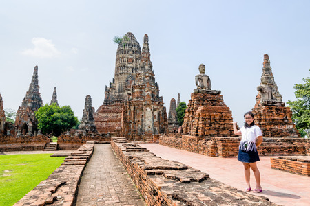 Tourist teenage girl show hand inviting to visit Wat Chaiwatthanaram is buddhist ancient temple, famous and major tourist attraction religion, Phra Nakhon Si Ayutthaya Historical Park, Thailand