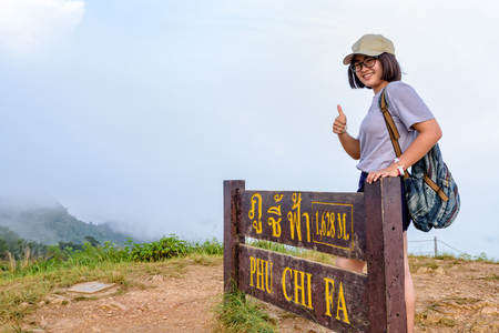 Tourist teen girl hiker wear caps and glasses with backpack smiling thumb up near nameplate attractions of Phu Chi Fa Forest Park on mountain and mist background, Chiang Rai, Thailand Stock Photo
