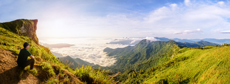blue widescreen widescreen: Panorama beautiful landscape nature, Male tourist are watching the sunrise on peak mountain with sun cloud fog and bright sky in winter at Phu Chi Fa Forest Park, famous attraction of Chiang Rai Province, Thailand