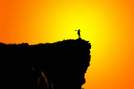 Black silhouette on orange and yellow background of woman tourist standing arms outstretched happy with success on peak mountain near the cliff at Phu Chi Fa Viewpoint, Chiang Rai, Thailand Stock Photo