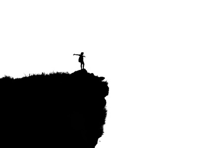 Black and white silhouette background of woman tourist standing arms outstretched happy with success on peak mountain near the cliff at Phu Chi Fa Viewpoint in Chiang Rai Province, Thailand