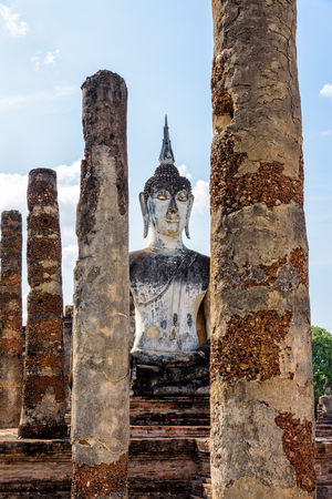 Ancient Buddha statue sitting among the ruins under the bright sky of Wat Maha That temple in Sukhothai Historical Park is an old city and famous tourist attraction of Sukhothai Province, Thailand Stock Photo