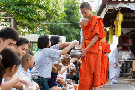 PHAYAO, THAILAND-OCTOBER 24, 2016: Mother daughter and thai buddhists are making merit with offer sticky rice and food to monk bowl in the morning, OCTOBER 24, 2016 in Thailand Editorial