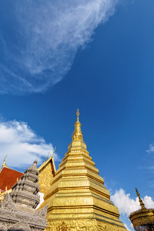 Wat Phra That Cho Hae Buddhism Temple with golden pagoda on blue sky background. Places worship of buddhists and attractions famous religion at Phrae Province, Thailand Stock Photo