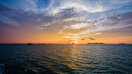 Beautiful natural landscape of colorful cloud sky and sun at sunset over the sea in Surat Thani province, Thailand, 16:9 widescreen