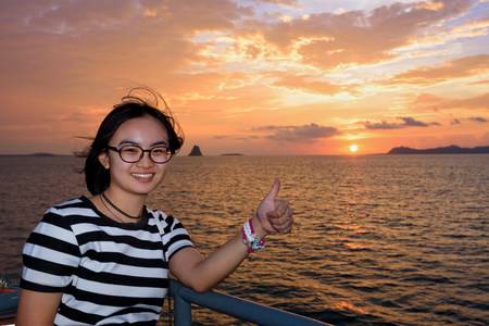 Women raise their thumb to admire the beautiful nature of colorful sky and sun at sunset over the sea on the deck of a passenger boat while cruising to Koh Samui Island in Surat Thani, Thailand Stock Photo