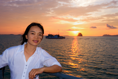 Beautiful nature of colorful sky and sun at sunset over the sea, women tourist on the deck of a large passenger boat while cruising to Koh Samui Island in Surat Thani province, Thailand