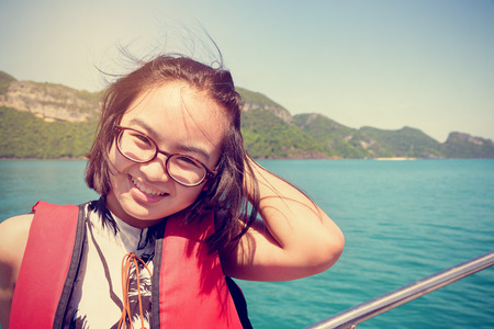 Vintage style young woman with eyeglasses smiling happily on the boat while cruising the natural of the sea and island in summer at Mu Ko Ang Thong National Park, Surat Thani, Thailand