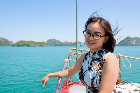 Cute young woman with eyeglasses smiling happily on the prow boat while cruising the beautiful natural of the blue sea and sky in summer at Mu Ko Ang Thong National Park, Surat Thani, Thailand Stock Photo