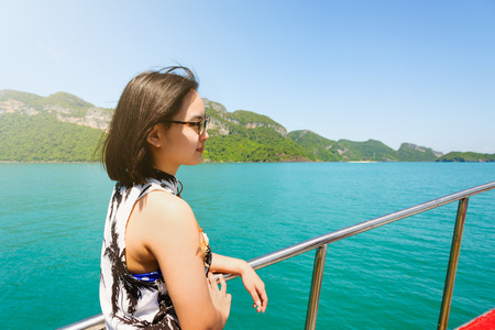 Cute young woman with eyeglasses smiling happily on the boat while cruising the natural of the sea island and under sunlight summer at Mu Ko Ang Thong National Park, Surat Thani, Thailand