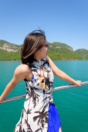 Cute young woman with eyeglasses smiling happily on the boat while cruising the beautiful natural of the blue sea and sky in summer at Mu Ko Ang Thong National Park, Surat Thani, Thailand Stock Photo