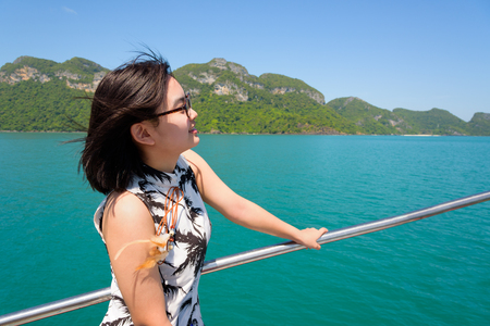cruising: Cute young woman with eyeglasses smiling happily on the boat while cruising the beautiful natural of the blue sea and sky in summer at Mu Ko Ang Thong National Park, Surat Thani, Thailand Stock Photo