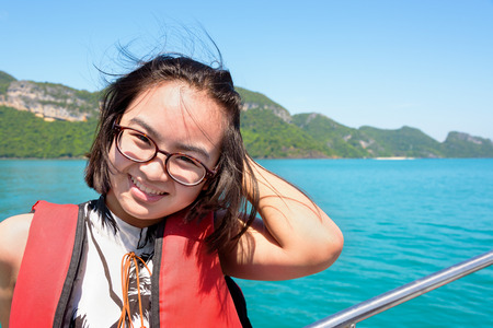 Cute young woman with eyeglasses smiling happily on the boat while cruising the beautiful natural of the blue sea and sky in summer at Mu Ko Ang Thong National Park, Surat Thani, Thailand Zdjęcie Seryjne