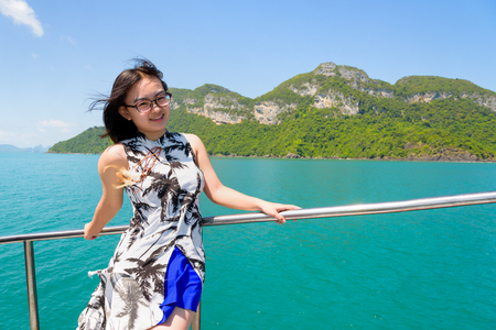 Asian young woman with eyeglasses smiling happily on the boat while cruising the beautiful natural of the blue sea and sky in summer at Mu Ko Ang Thong National Park, Surat Thani, Thailand